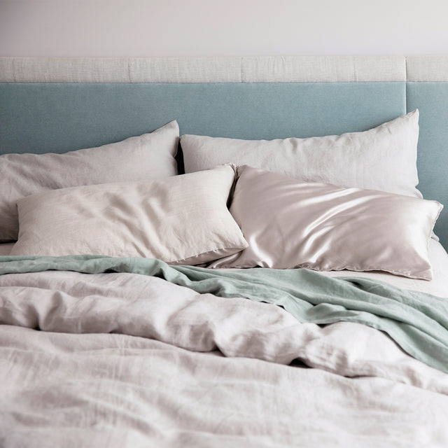 Smoke Grey duvet cover set and Smoke Grey silk linen flip pillowcases styled on a bed.
