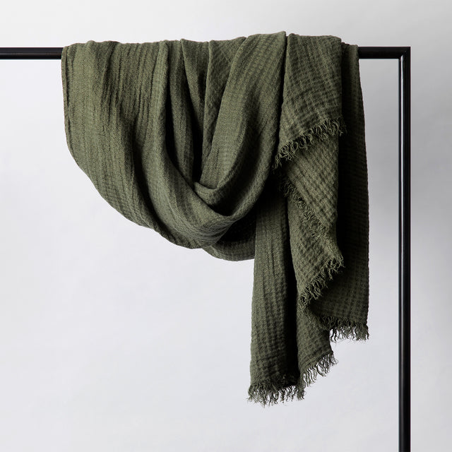 Estela Linen Waffle Throw in Forest hanging on a rail