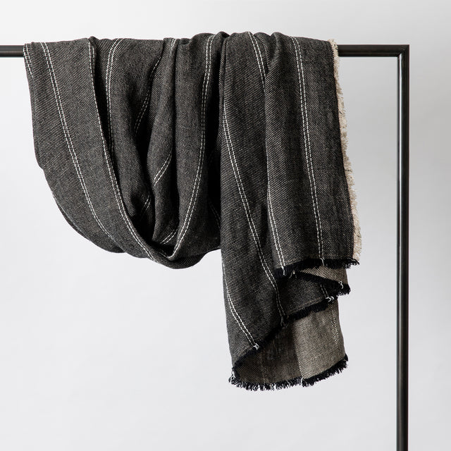Mira Linen Throw in Rafa hanging over a rail.