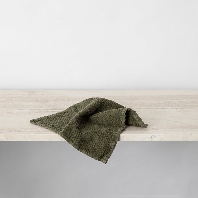 Forest Pure Linen Wash Cloth hanging off ledge.