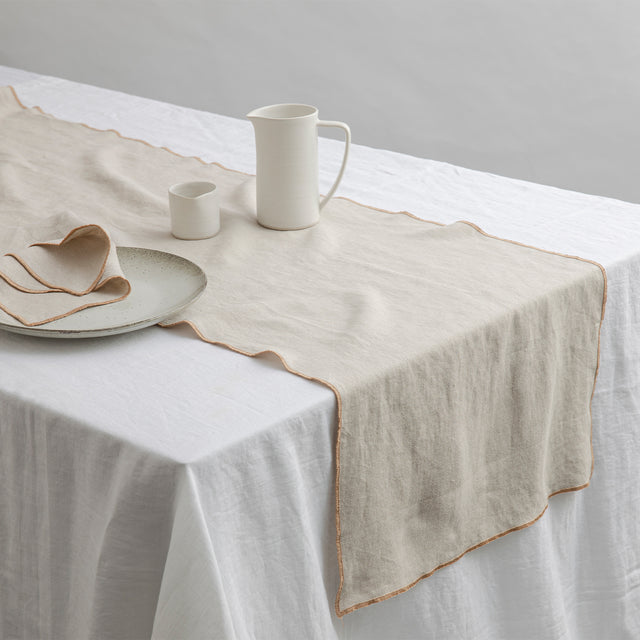 Cara Edged Table Runner in Natural on a Linen Tablecloth in White