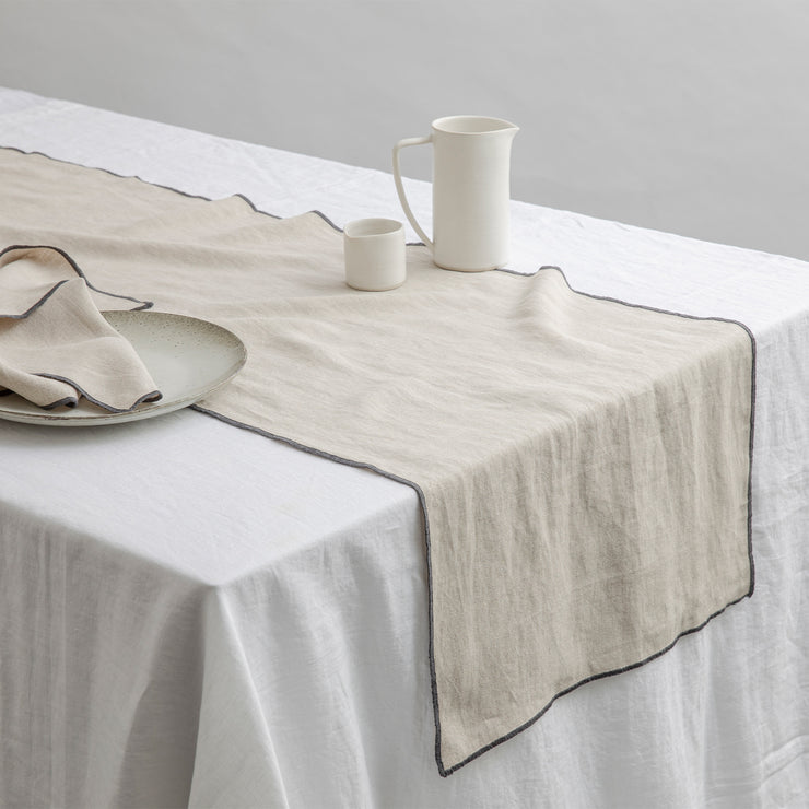 Cara Edged Table Runner in Slate on a Linen Tablecloth in White