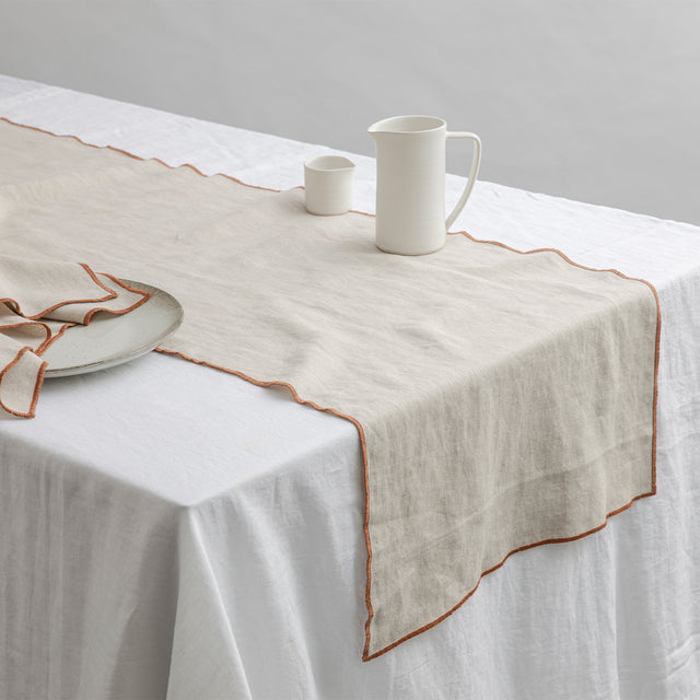 Cara Edged Table Runner in Cedar on a Linen Tablecloth in White