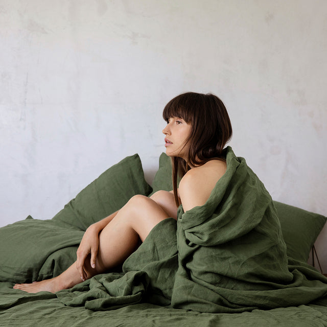 A model with fair skin and dark brown hair is sitting in a bed wrapped up in the duvet cover. The bed is styled with a Forest Linen Sheet Set with Pillowcases and Linen Duvet Cover.