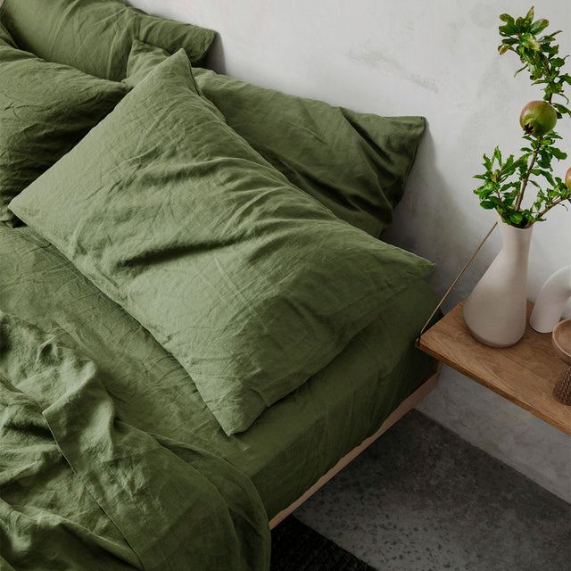 A close up of a bed styled with a Linen Flat Sheet with Border, Linen Fitted Sheet and Linen Pillowcases in Forest. Next to the bed is a hanging wooden shelf, styled with a white vase containing some green branches.