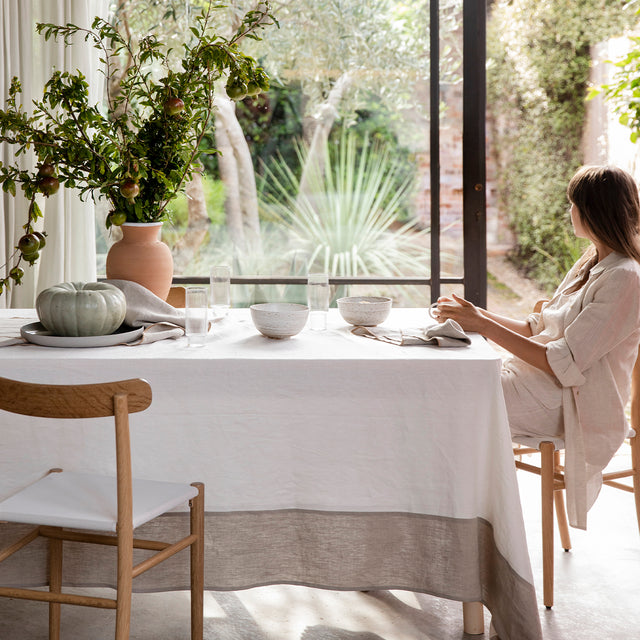 Model dressed in all beige linen sitting at a table covered in the Cara Panel Tablecloth. On top of the table are some ceramic bowls, glasses, Cara Edged Napkins in Natural, a terracotta vase of pomegranates and a large pumpkin on a grey plate/dish. The model is looking out the window at the greenery outside.