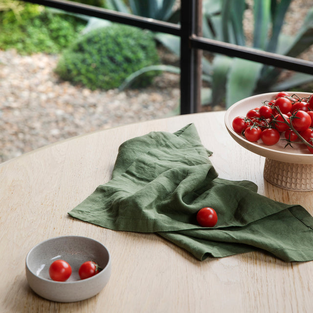 A Linen Table Napkin in Forest on a wooden table. Next to the napkin is a small dish of tomatoes and a larger stand of tomatoes.