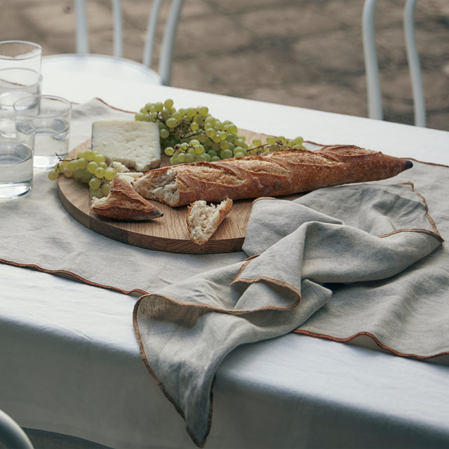 An outdoor table dressed in the Cara Panel Tablecloth, Cara Edged Table Runner in Cedar and a Cara Edged Napkin in Natural. On top of the table linen is a round wooden board of cheese, grapes and a baguette.