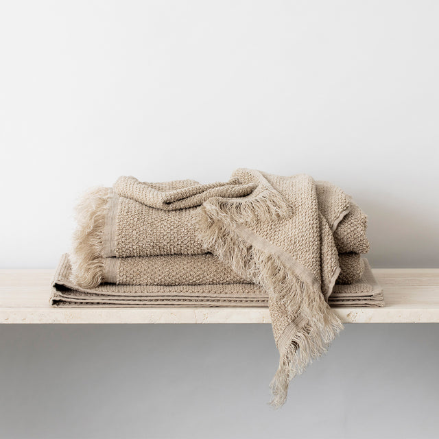 Stack of Pure Linen Towels and a Bath Mat in Natural