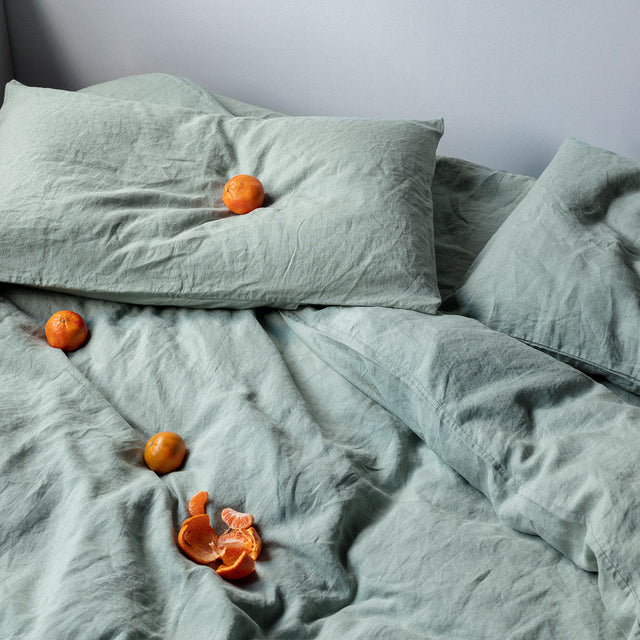 Sage sheet set styled on a bed with Mandarins scattered on the Duvet Cover.