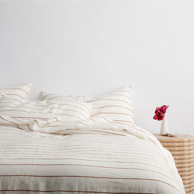 Bed styled with Cedar Stripe Duvet Cover Set and Cedar Stripe Sheet Set, featuring a bedside table with a flower in a vase.