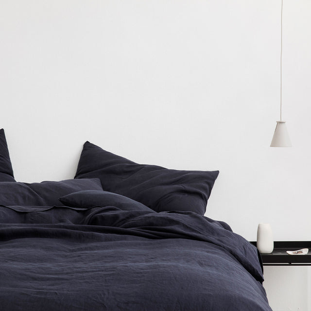 Bed styled with Navy Duvet Cover Set and Navy Sheet Set, a low hanging light and bedside table sits next to the bed.