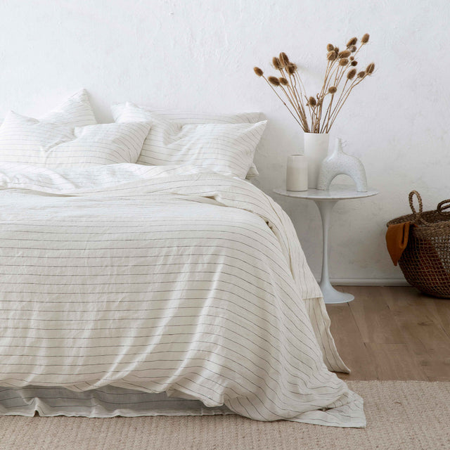 Bed styled in Linen Duvet Cover Set and Linen Sheet Set in Pencil Stripe. On the bedside table is a ceramic vase with flowers and ceramic object. There is a basket on the floor.
