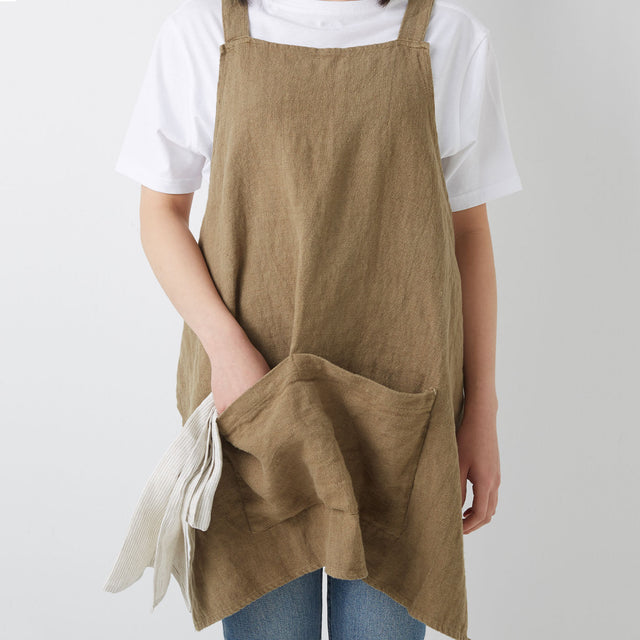 Model wears Jude Linen Apron in Olive colour