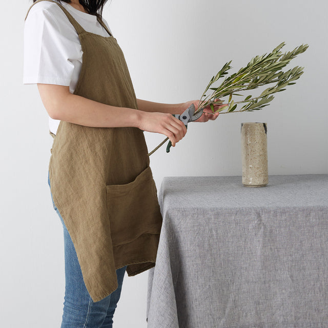 Model wears Jude Apron in olive colour