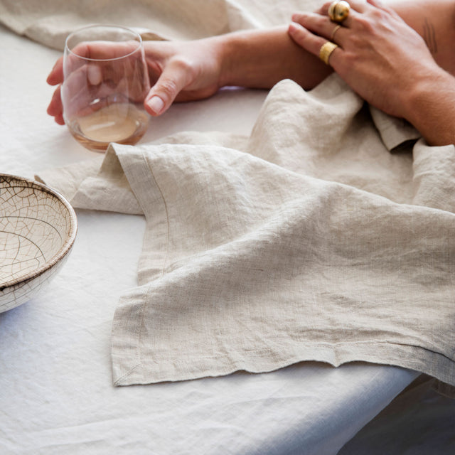 A close up on the Linen Table Napkin in Natural on top of a Linen Tablecloth in White. On top of the napkin are two hands, one is adorned in gold rings and the other is holding a glass.