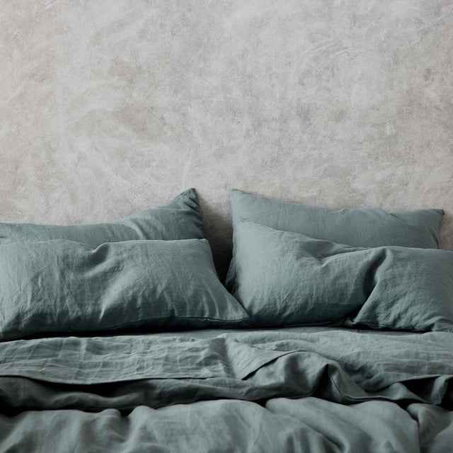 Set of 2 Linen Pillowcases  and Duvet Cover Set in Bluestone on a bed.