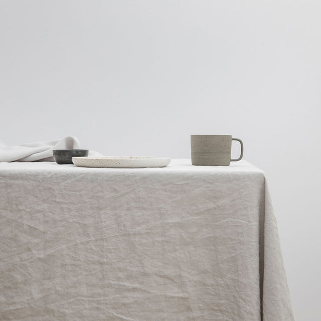 The Linen Tablecloth in Smoke Grey styled with a white ceramic plate and grey ceramic mug.