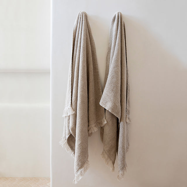 Two Pure Linen Bath Towels in Natural hanging on hooks on a white wall.