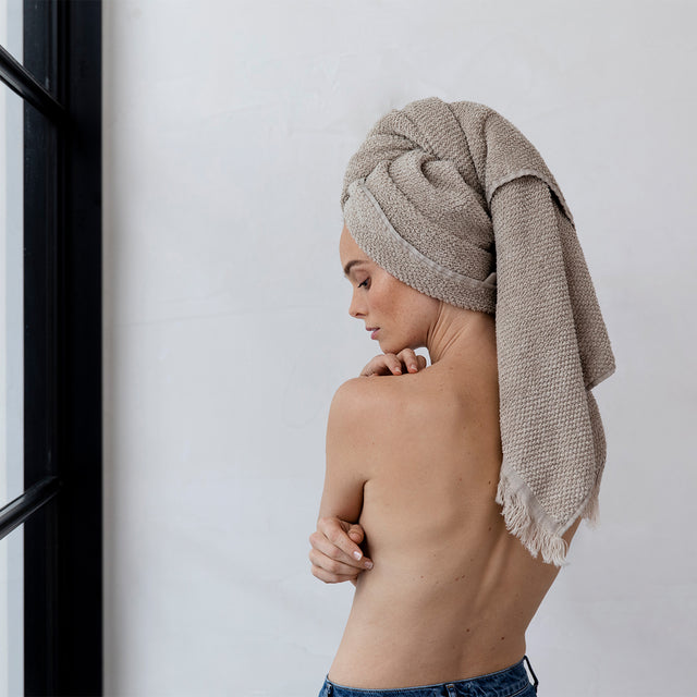 A model is standing with her back to the camera. She isn't wearing a shirt, and has a Pure Linen Bath Towel in Natural wrapped around her hair.