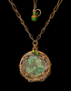 A pendant made with the Berry Ring. Swirling Flowers grace the inside.