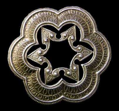 Brass stamping of a scalloped ring with a decorative star center