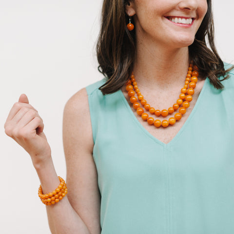 Amber Orange Jade Jewelry on Model wearing Turquoise Blouse