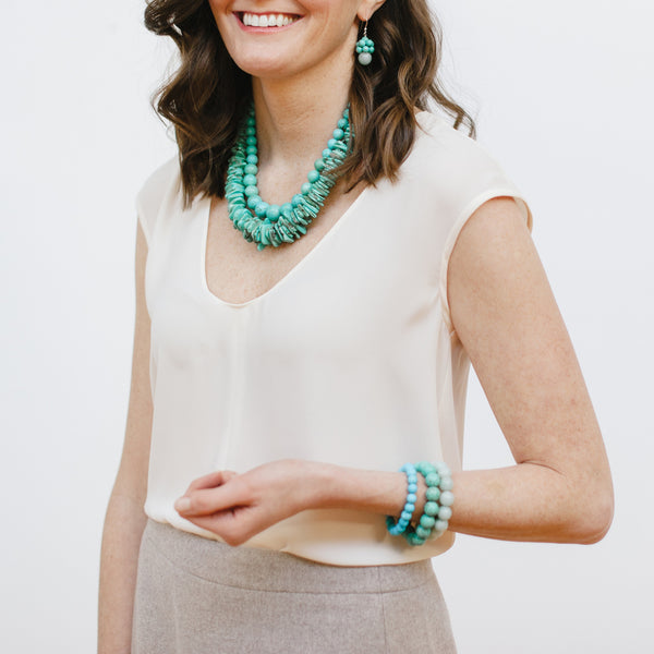 Turquoise Stone Jewelry on a Model wearing Cream Blouse