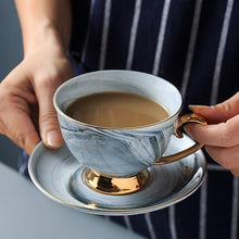 Load image into Gallery viewer, Beautiful traditional cup with gold pedestal and handle. Cup and saucer have a gold trim that reflects chic and elegance. This is the perfect marble cup and saucer that you'll want to use every day for your daily coffee or tea.
