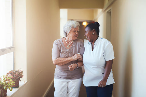 Woman & Caregiver Walking Arm-in-Arm