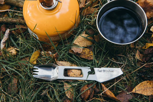 The muncher titanium camping multi utensil next to coffee cup and gas stove