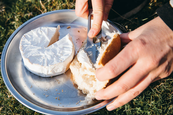 camabert cheese being spread onto bread using the muncher titanium camping multi utensil