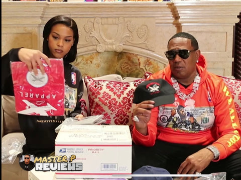 Master P sitting on a couch with a female co host holding the best clothing brand in the world. The shirt red with a white design. Master P is holding a black hat with a multi color plane logo with Corner kids apparel on the front.