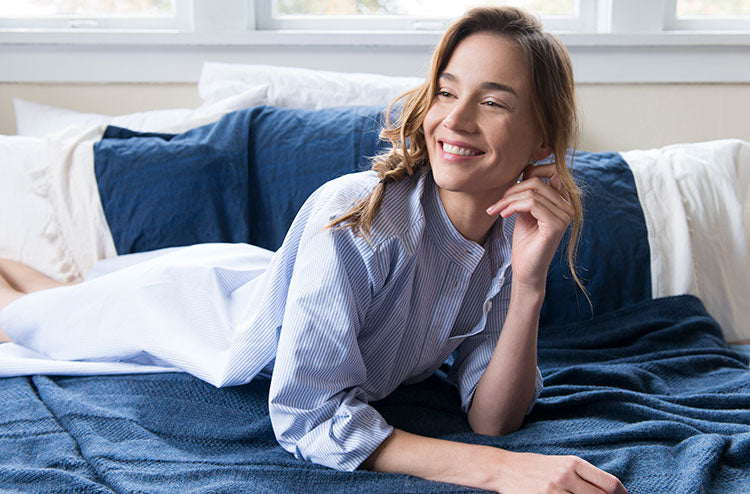 Model lying on bed wearing best selling long sleep shirt in popular Blue Oxford Stripe cotton