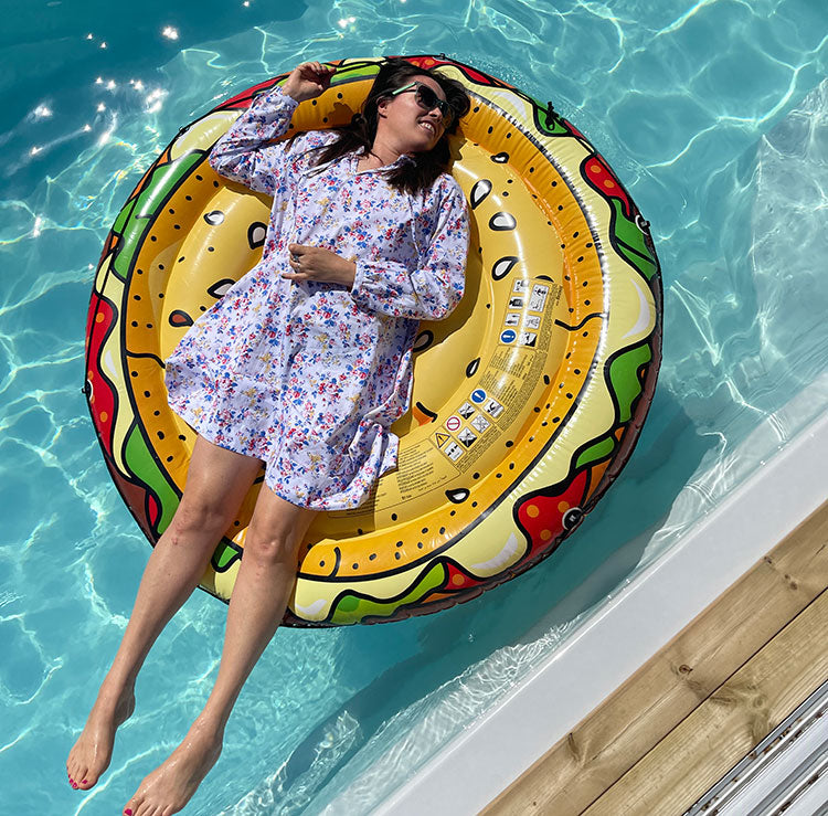 A woman wears a floral dress while laying on an inflatable in a pool