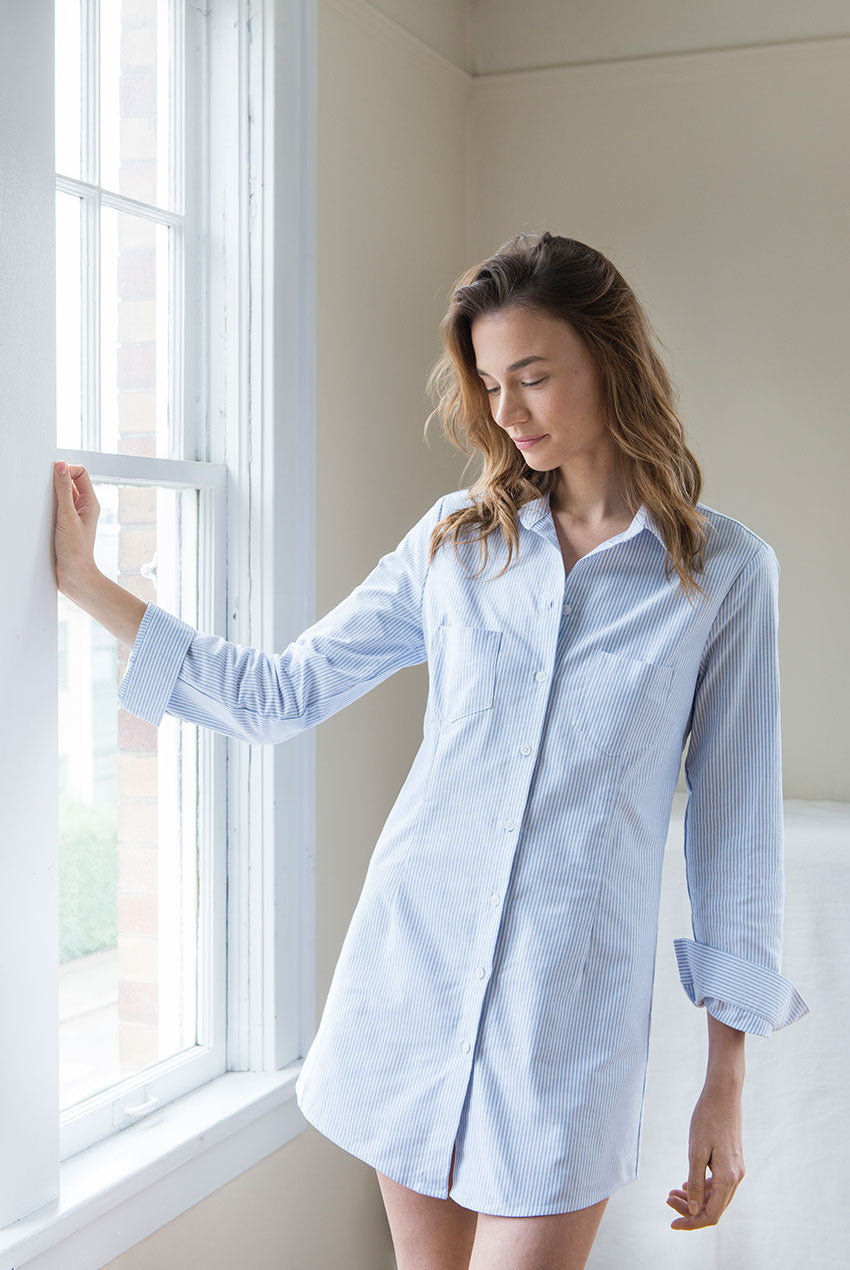 Model leaning on window frame in Slim Sleep Shirt in Blue Oxford Stripe cotton
