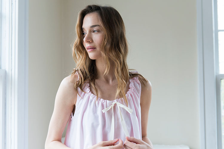 Model wearing popular Sleeveless Nightie in Pink Oxford Stripe touching bow on the front collar