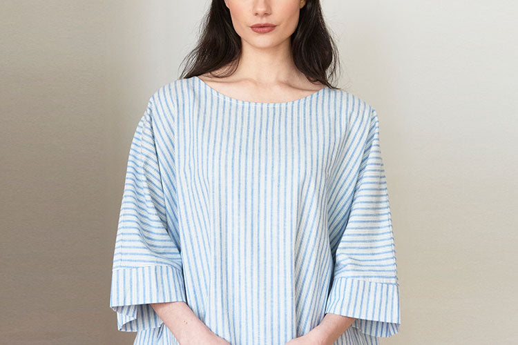 Woman in striped cotton linen kaftan with pockets
