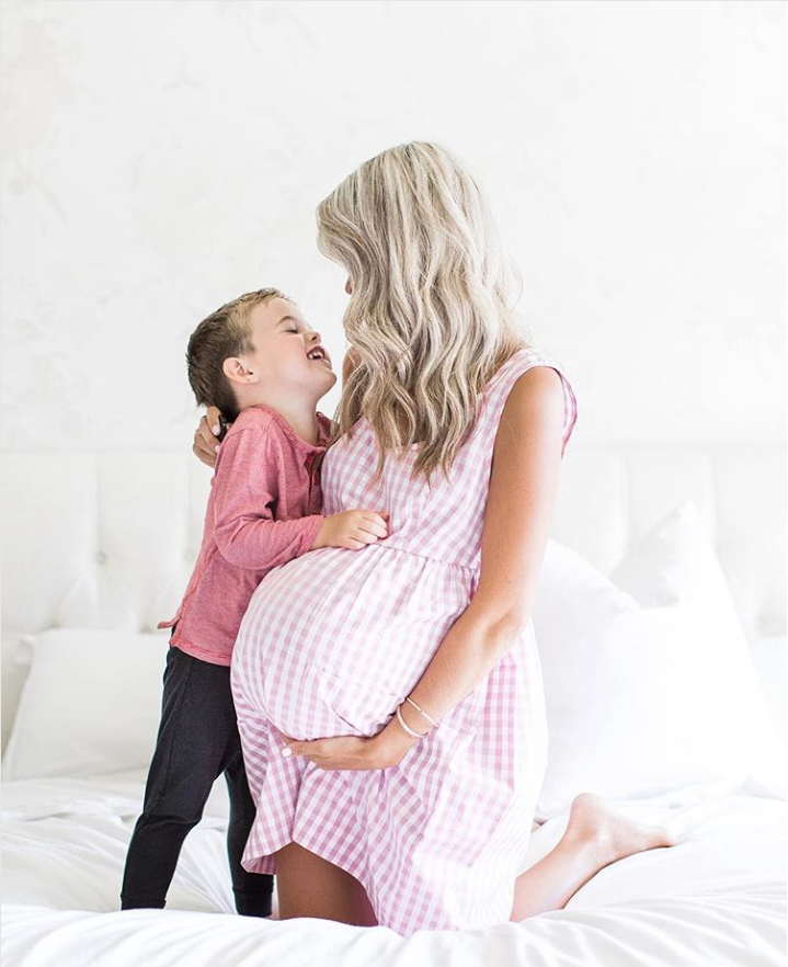 Pregnant mother with toddler hugging on bed in Pocket Nightie in rosy pink gingham