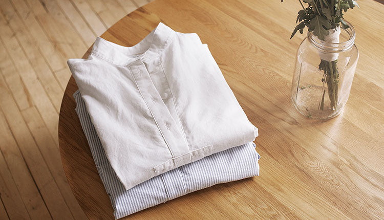 Folded cotton nightshirts on a wood table