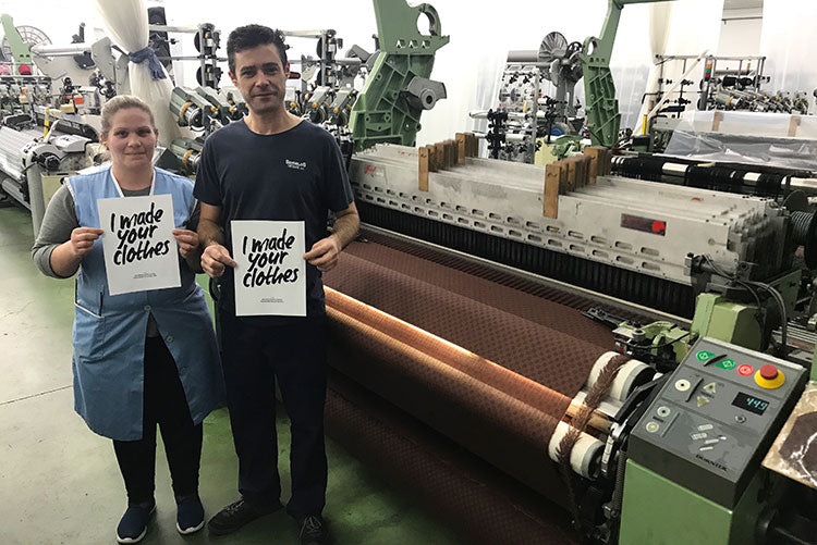 Two people stand next to a fabric weaving machine