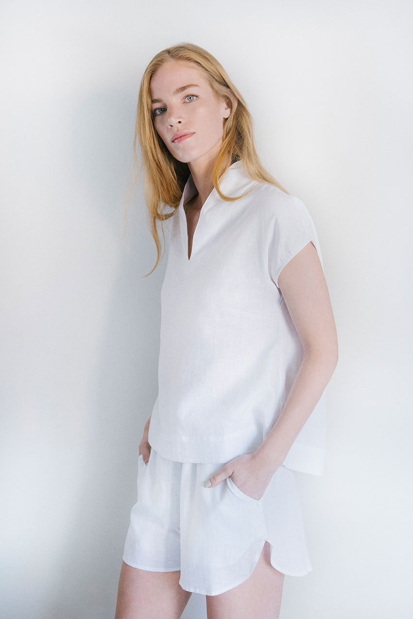 Hands in pockets of the Curve Hem Shorts White Linen with matching Shawl Coller Top