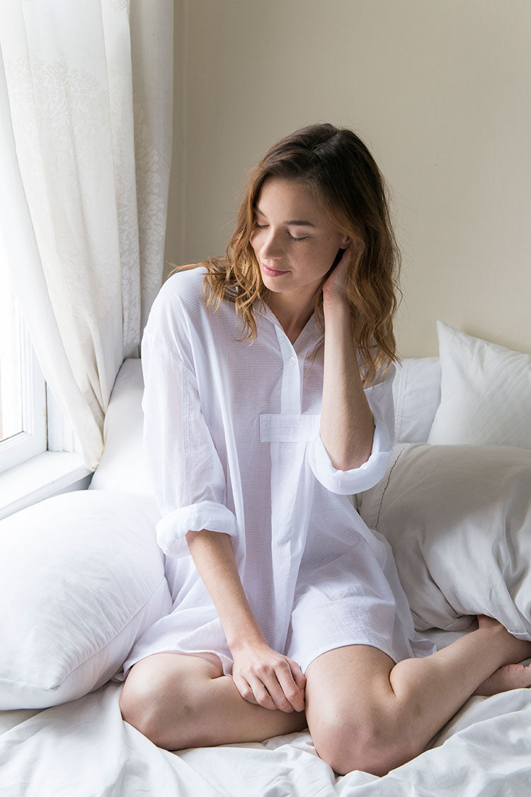 Model in bed touching hair wearing the Short Sleep Shirt in Sheer Pencil Stripe white cotton