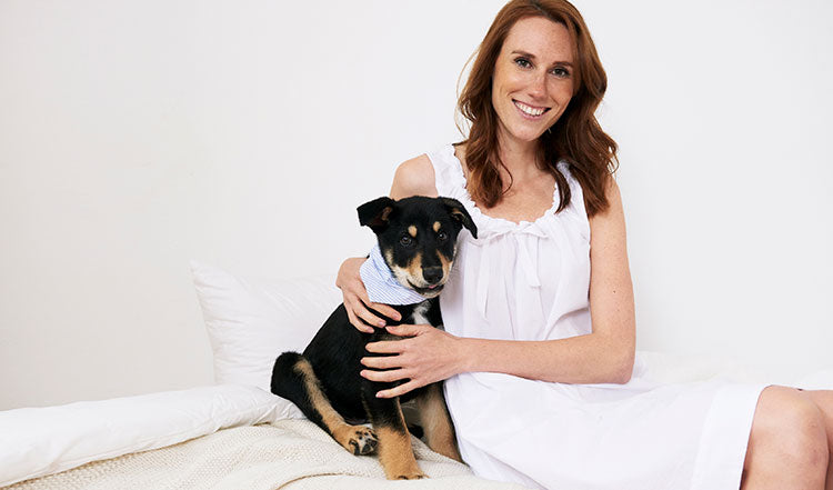 a woman wears a white cotton nightie and hugs a puppy