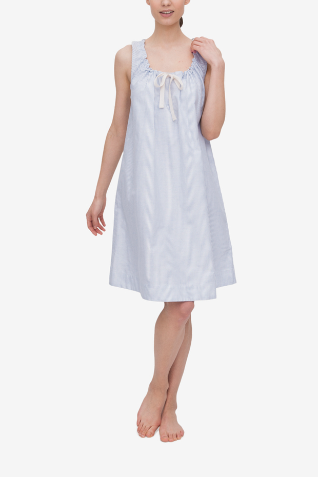 Front view of the Sleeveless Nightie in Blue Oxford Stripe. The model has one arm at her side and the other hand up at the shoulder, highlighting the gathered neckline.