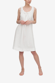 Front view of the Sleeveless Nightie, it's knee length and has a unique gathered necking with the bow tied at centre front. Shown here in a classic white royal oxford shirting, a fabric with great texture and drape.