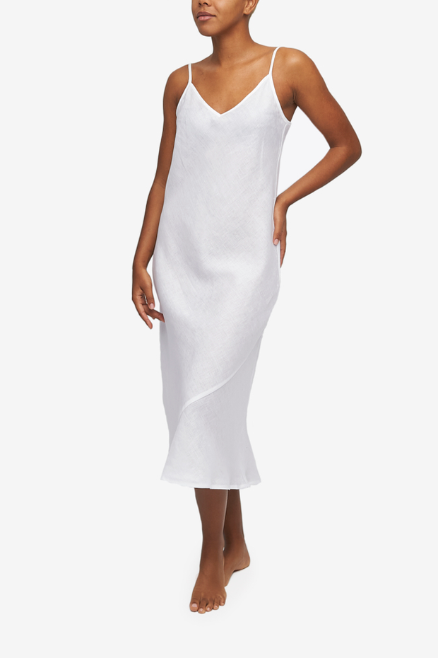 A midi length, V-neck slip dress with adjustable spaghetti straps. Made form out timeless White Linen and cut on the bias for ultimate fit.