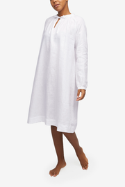 Full shot of a black woman with a blonde buzz cut,  wearing a knee-length nightgown with raglan sleeves with button cuffs. There is a little bow at the centre front of the gathered neck line. Made in our favourite, crisp white linen.
