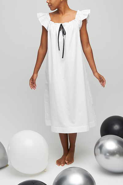 A below-the-knee length nightdress with short flounce sleeves and gathered neckline. Made in a classic seersucker cotton in white.