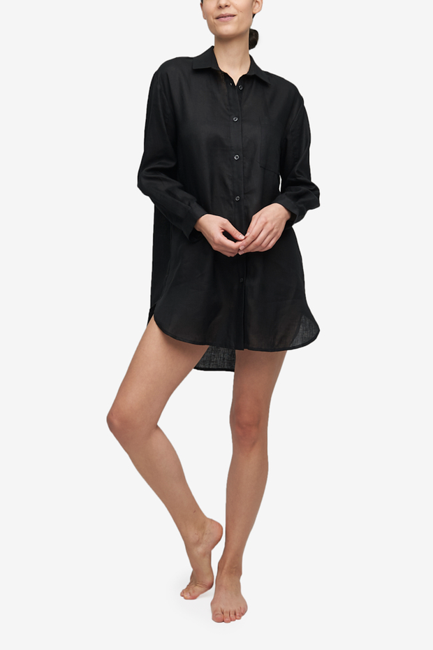 Woman wearing a black linen button up Classic Sleep Shirt with a traditional pointed shirt collar. Long, cuffed sleeves, and a curved hem that's long enough to cover your bottom.